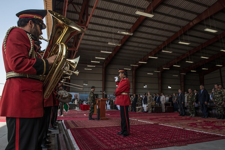 Afghan senior government and international military officials stand while the Afghan National Security and Defense Forces band plays during the beginning of the official arrival ceremony for the first UH-60 Black Hawk helicopters to the country, Oct. 7, 2017, at Kandahar Airfield, Afghanistan. Leaders signed an official transfer of ownership and performed a ceremonial ribbon cutting celebrating the newest addition to Afghanistan's young air force fleet. (U.S. Air Force photo by Staff Sgt. Alexander W. Riedel)