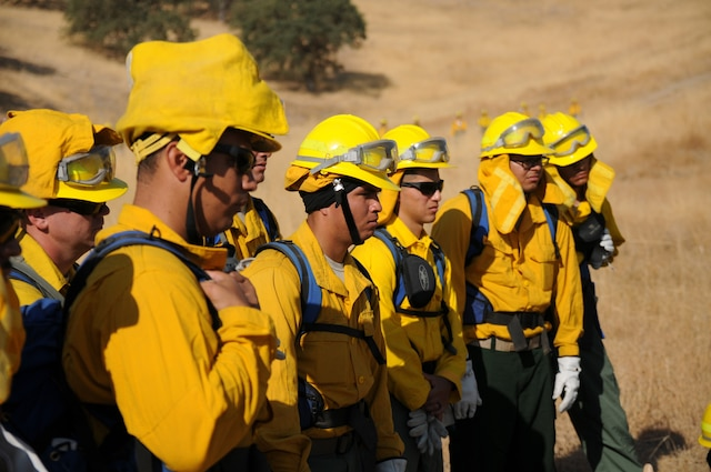Firefighters wearing yellow shirts and helmets stand together outside while listening to a briefing.