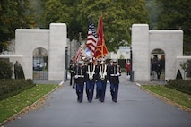 Marine Color Guard from Marine Corps Forces Europe and Africa march through the gate of the Aisne-Marne American Cemetery and Memorial during a wreath laying ceremony conducted by the Ancient and Honorable Artillery Company of Massachusetts in Belleau, France, Oct. 1, 2017. U.S. Marine Corps Forces Europe and Africa routinely conducts theater engagement and outreach throughout its Area of Responsibility, and provided a Color Guard and Rifle Detail for the event that took place at the foot of the hill where the Battle of Belleau Wood was fought. (U.S. Marine Corps photo by 2ndLt. Brett Lazaroff/Released)
