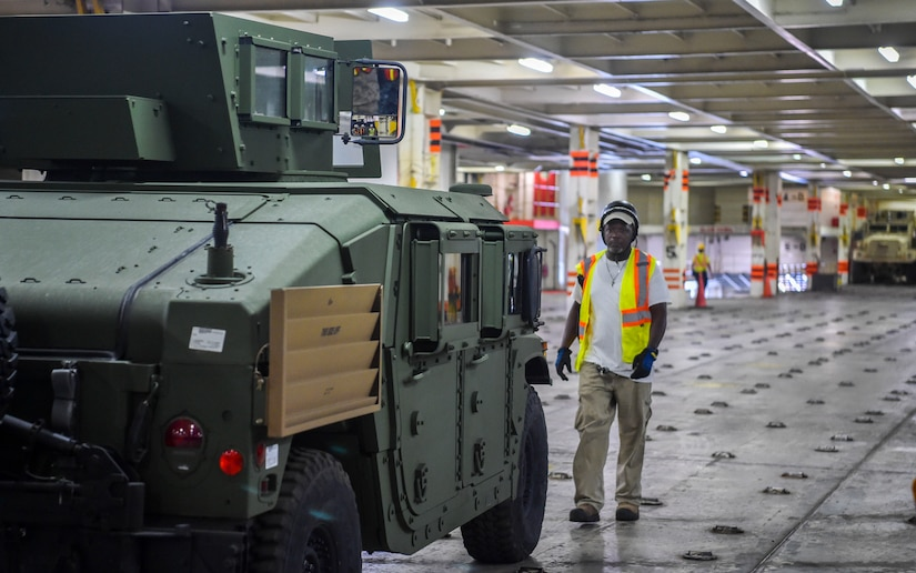 A civilian contractor lines up a military vehicle during an on-load at Joint Base Charleston-Weapons Station, S.C., Sept. 27, 2017.