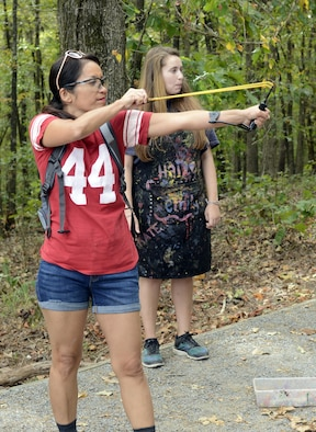 A woman fires a slingshot as another woman watches behind her.