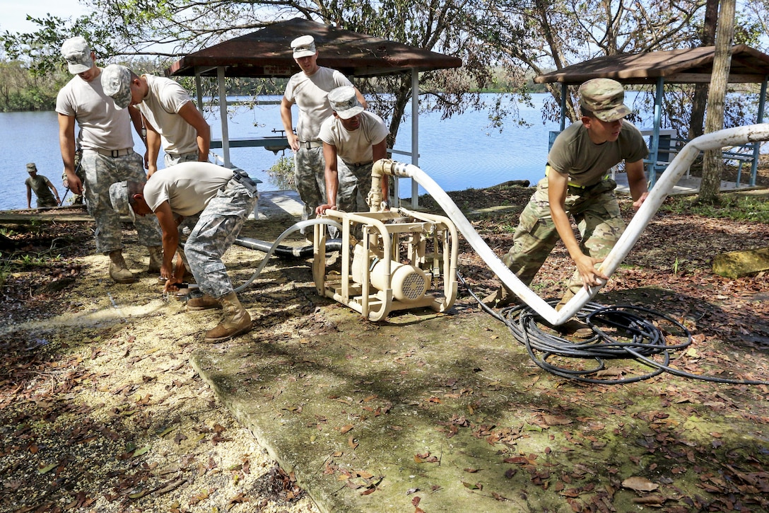 Soldiers use equipment to purify water from a lake.