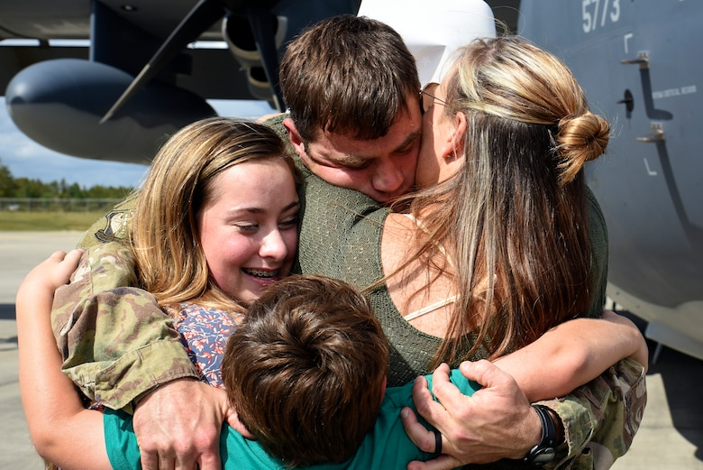 Tech. Sgt. James Anderson, 23d Equipment Maintenance Squadron aircraft structural maintainer, hugs his family during a redeployment, Oct. 6, 2017, at Moody Air Force Base, Ga. Airmen from the 71st Rescue Squadron (RQS) supported deployed operations by providing expeditionary personnel with on-call recovery forces should they need to be rescued. (U.S. Air Force photo by Senior Airman Greg Nash)