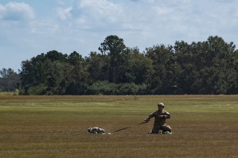 Tech. Sgt. Vanloon, 820th Combat Operations Squadron NCO in charge of individual combat equipment, gathers a MC-6 parachute after a static-line jump, Oct. 3, 2017, at the Lee Fulp drop zone in Tifton, Ga. During a static-line jump, the jumper is attached to the aircraft via the 'static-line', which automatically deploys the jumpers' parachute after they've exited the aircraft. (U.S. Air Force photo by Airman 1st Class Daniel Snider)