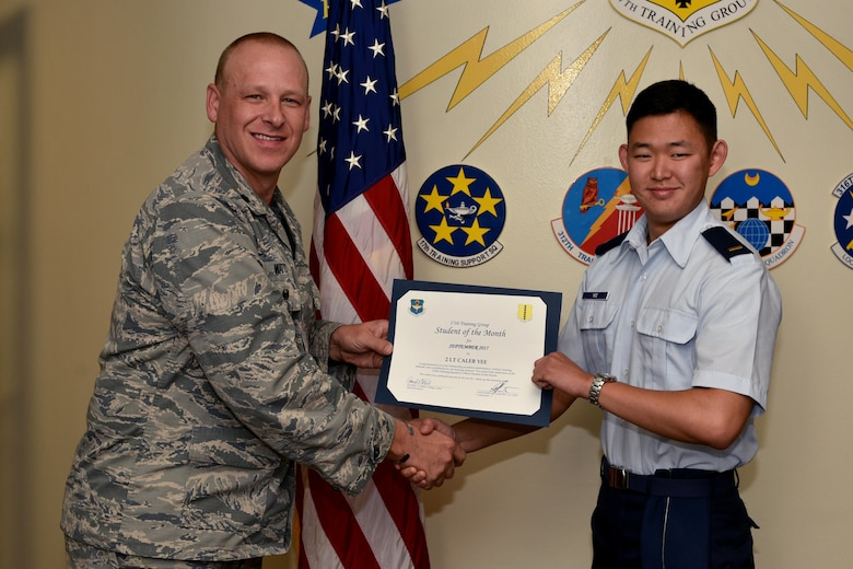 U.S. Air Force Lt. Col. Steven Watts, 17th Training Group deputy commander, presents the 315th Training Squadron Officer Student of the Month award for Sept. 2017 to 2nd Lt. Caleb Yee, 315th Training Squadron trainee, in the Brandenburg Hall on Goodfellow Air Force Base, Texas, Oct. 5, 2017. The 17th Training Wing's mission is to develop and inspire exceptional intelligence, surveillance and reconnaissance, and fire protection professionals for America and her allies. (U.S. Air Force photo by Airman 1st Class Randall Moose/released)