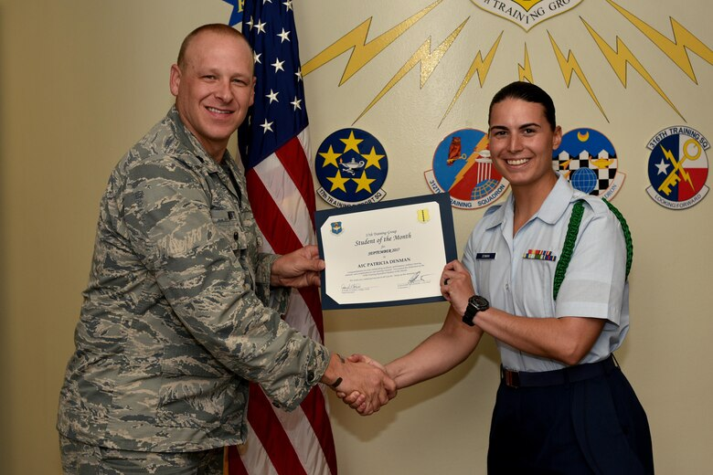 U.S. Air Force Lt. Col. Steven Watts, 17th Training Group deputy commander, 315th Training Squadron Student of the Month award for Sept. 2017 to Airman Patricia Denman, 315th Training Squadron trainee, in the Brandenburg Hall on Goodfellow Air Force Base, Texas, Oct. 5, 2017. The 17th Training Wing's mission is to develop and inspire exceptional intelligence, surveillance and reconnaissance, and fire protection professionals for America and her allies. (U.S. Air Force photo by Airman 1st Class Randall Moose/released)
