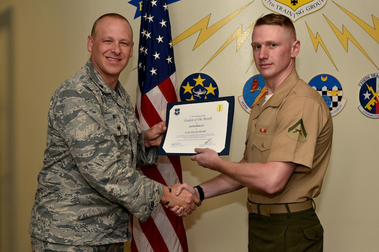 U.S. Air Force Lt. Col. Steven Watts, 17th Training Group deputy commander, 315th Training Squadron Student of the Month award for Sept. 2017 to U.S. Marine Corps Lance Cpl. Dylan Busby, 316th Training Squadron trainee, in the Brandenburg Hall on Goodfellow Air Force Base, Texas, Oct. 5, 2017. The 17th Training Wing's mission is to develop and inspire exceptional intelligence, surveillance and reconnaissance, and fire protection professionals for America and her allies. (U.S. Air Force photo by Airman 1st Class Randall Moose/released)