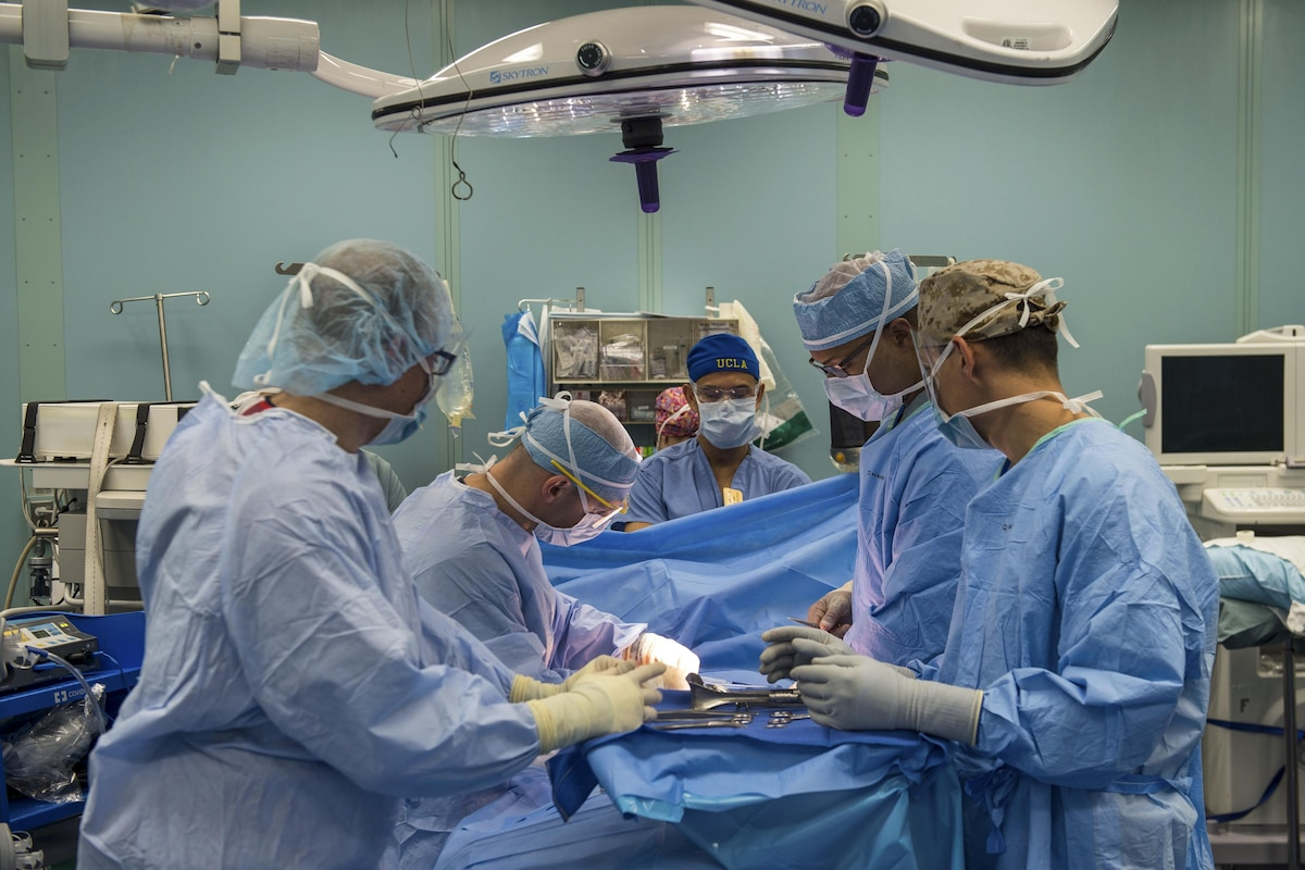 Sailors perform a surgical operation aboard a ship.