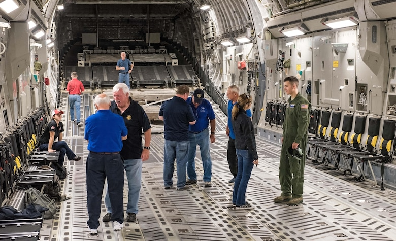 Senior Airman Andrew Gwinn, 3d Airlift Squadron loadmaster, answers questions from NASCAR team members about the C-17 Globemaster III and his duties Sept. 28, 2017, on Dover Air Force Base, Del. Gwinn was a member of a 3d AS aircrew that took more than 20 participants on a NASCAR orientation flight. (U.S. Air Force photo by Roland Balik)