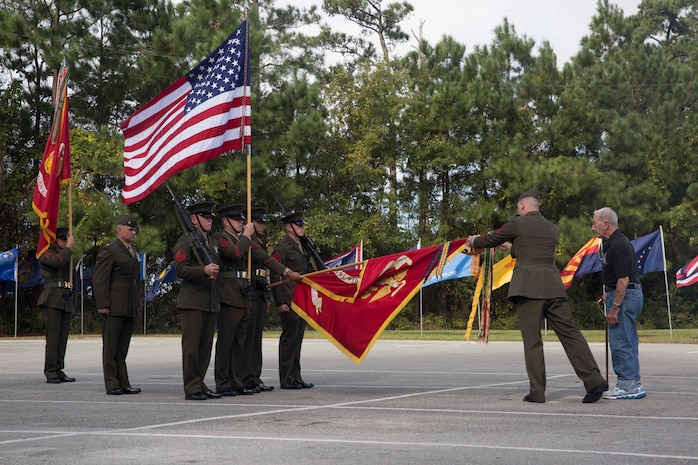 A retired Marine who served with 8th Marine Regiment is escorted to place a banner on the 8th Marine Regiment flag during the unit's 100th anniversary ceremony at Camp Lejeune, N.C., Oct. 6, 2017. Marines of past and present gathered to commemorate the 100th anniversary of the inception of 8th Marine Regiment. The unit was established Oct. 9, 1917. (U.S. Marine Corps photo by Pfc. Nicholas Guevara)