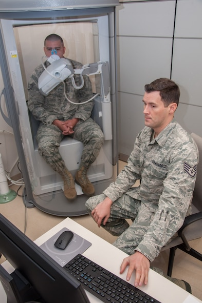 Staff Sgt. Jonathon Lee, pulmonary technician with the Aeromedical Consultation Service Internal Medicine Branch, conducts a demonstration of a pulmonary function test for forced vital capacity as Staff Sgt. Sean O'Neill sits in a pressurized cabin awaiting the command to exhale. The branch reviews around 700 requests for waiver recommendation cases annually concerning pilots, navigators and other aircrew, with 90 percent of them receiving waiver recommendations. (U.S. Air Force photo/John Harrington)