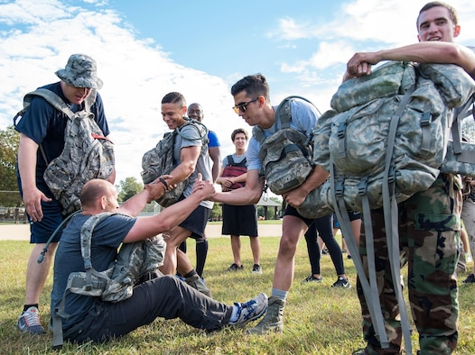 GORUCK participants help a member up after completing a warm-up exercise Oct. 6, 2017, at Brecknock Park in Camden, Del. Thirty-one individuals participated in the 2017 GORUCK Light Challenge that teaches participants how to overcome adversity by working as a team. (U.S. Air Force photo by Roland Balik)