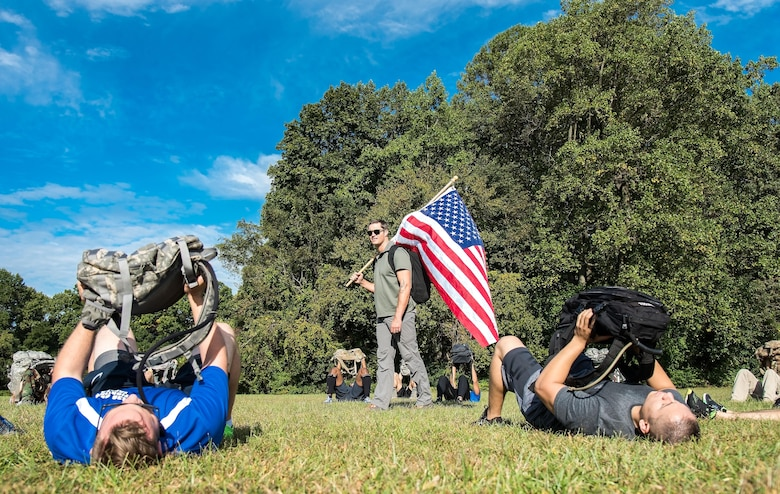 U.S. Army Master Sgt. Todd Fetzer, 1st Special Forces Command (Airborne), Ft. Bragg, N.C., watches GORUCK participants press their rucksack during warm-up exercises Oct. 6, 2017, at Brecknock Park in Camden, Del. Twenty-nine individuals completed the 2017 GORUCK Light Challenge. (U.S. Air Force photo by Roland Balik)