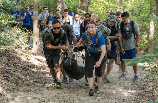 Working in teams, participants in the 2017 GORUCK Light Challenge carried a punching bag while completing three laps on the hiking trail Oct. 6, 2017, at Brecknock Park in Camden, Del. Participants completed the laps while carrying their rucksack, chains and a punching bag. (U.S. Air Force photo by Roland Balik)