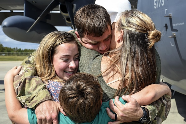 An airman hugs several members of his family.