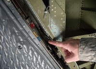 Master Sgt. D.J. Little, a 94th Maintenance Squadron hydraulic technician, points out the small space that houses the actuator on a C-5M Super Galaxy at Dobbins Air Reserve Base, Ga. Oct. 6, 2017. Little worked with technicians from Dover Air Force Base, Dela. on creating custom-sized hydraulic hoses to bypass the actuator so that it could be replaced. The actuator is needed to open and close the visor of the aircraft so that cargo can be offloaded. In this case, the cargo included communication equipment for Puerto Rico. (U.S. Air Force photo/Staff Sgt. Andrew Park)