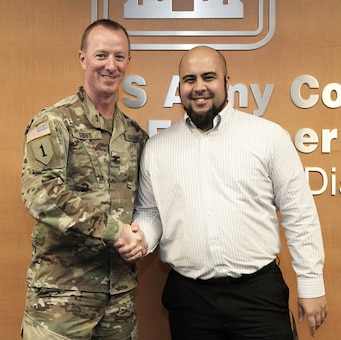Mike Robinson, contract specialist, U.S. Army Corps of Engineers Los Angeles District, right, is congratulated by Col. Kirk Gibbs, District commander, left, during the Oct. 5 End of the Year Celebration at the District headquarters in downtown LA.