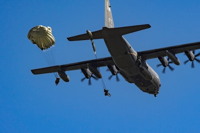 Members of the 820th Base Defense Group exit an HC-130J Combat King II during a static-line jump, Oct. 3, 2017, at the Lee Fulp drop zone in Tifton, Ga. During a static-line jump, the jumper is attached to the aircraft via the 'static-line', which automatically deploys the jumpers' parachute after they've exited the aircraft. (U.S. Air Force photo by Airman 1st Class Daniel Snider)