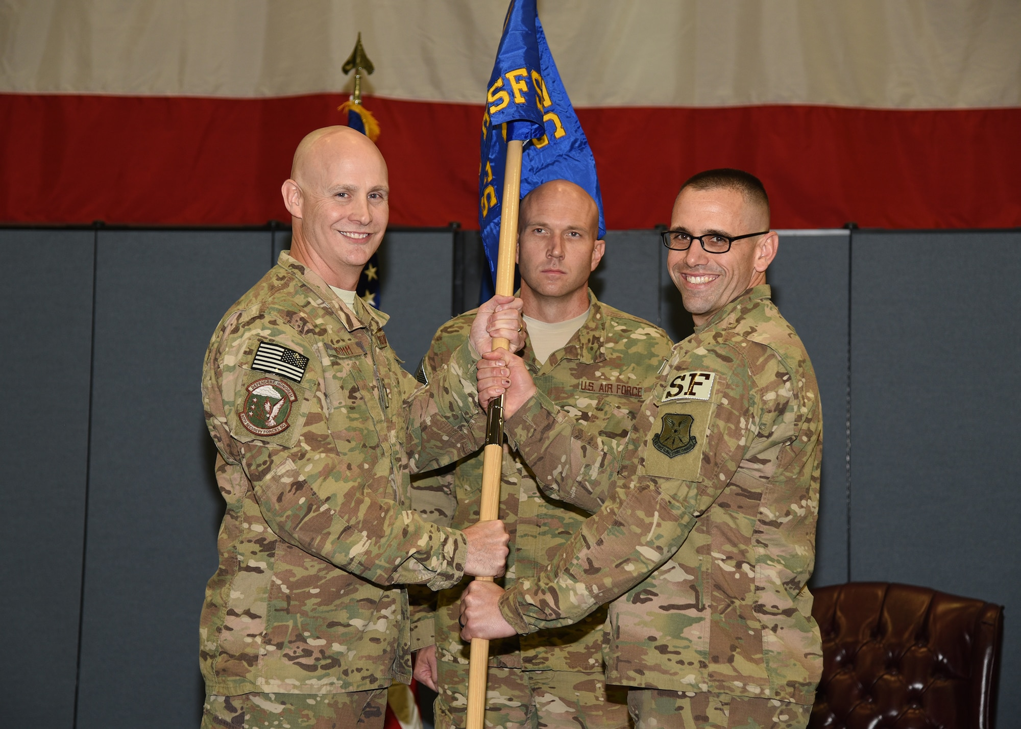 Colonel John Grimm, 90th Security Forces Group commander, passes the guidon to Major David Lycan, 890th Missile Security Forces Squadron commander, during the MSOC change and assumption of command ceremony at F.E. Warren Air Force Base, Wyo., Sept. 20, 2017.