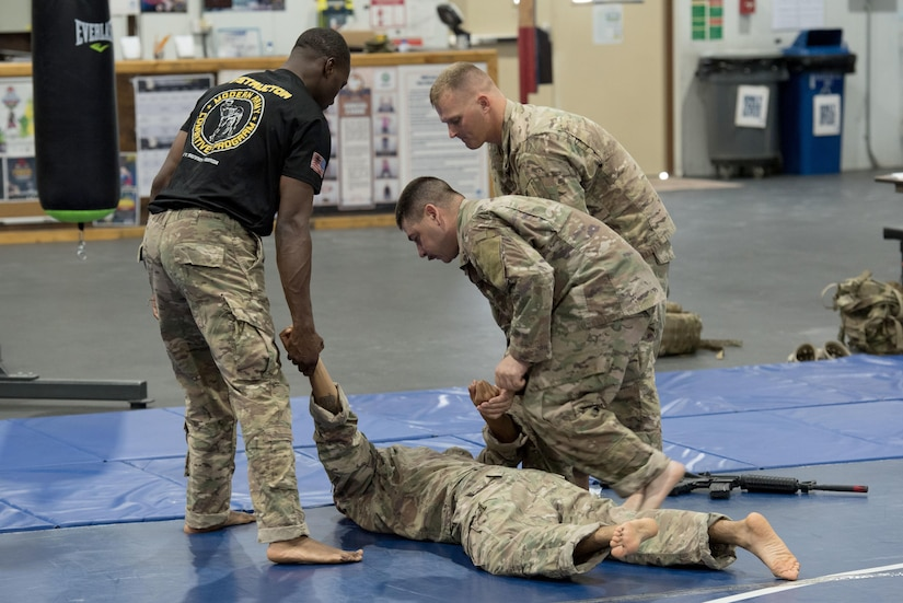 Instructor provides guidance to a group of Soldiers practicing hand-to-hand combat.