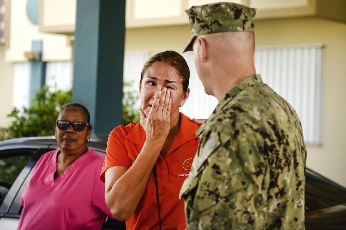 A woman cries as while talking with a service member.