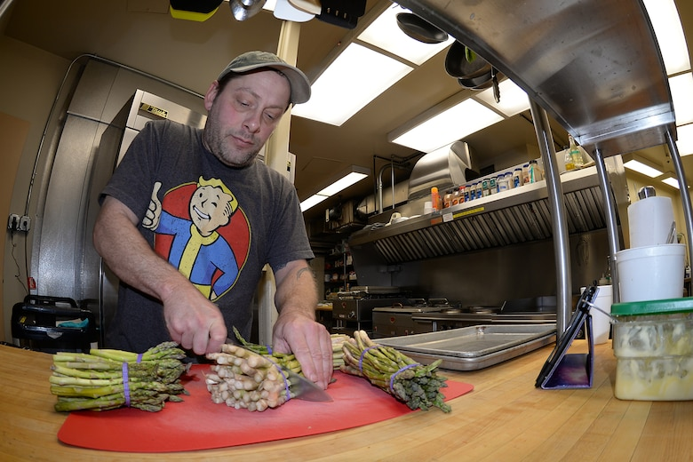 Sean Fenderson, ARCTEC services technician, chops asparagus in preparation for the evening meal on Sep. 27, 2017. The North Pole, Alaska, resident has worked at most radar sites operated by ARCTEC during his five year employment and is on his second assignment to Cape Romanzof. (U.S. Air Force photo by Alex R. Lloyd)