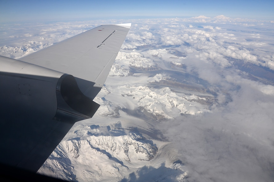 A chartered Cessna Conquest II aircraft flies over the Tordrillo Mountain Range on Sep. 25, 2017, on its way to Cape Romanzof, Alaska. Below the aircraft is Triumvirate Glacier and in the distance (top right) are the mountains Foraker and North America's highest mountain, Denali. (U.S. Air Force photo by Alex R. Lloyd)