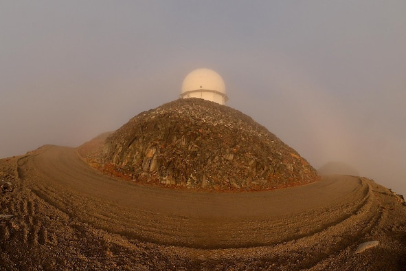 Sun, wind and clouds surround the long range radar radome at the top of Towak Mountain, Cape Romanzof, Alaska, on Sep. 26, 2017. The weather is the biggest factor that affects team members ability to accomplish their maintenance mission. (U.S. Air Force photo by Alex R. Lloyd)