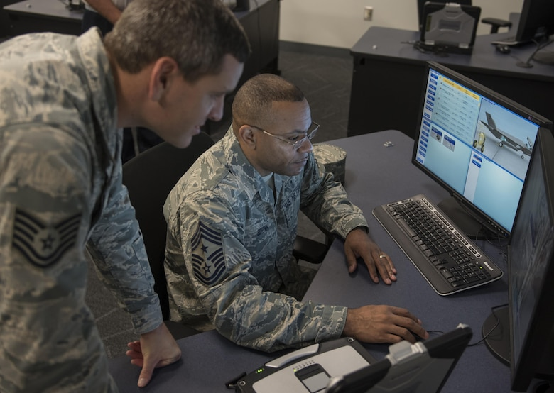 U.S. Air Force Tech. Sgt. Derek Mantzke, F-35 Academic Training Center avionics instructor, explains how to operate an Aircraft Systems Maintenance Trainer to Chief Master Sgt. David Brown, 19th AF command chief, Oct. 3, 2017, at Eglin Air Force Base, Fla. During Brown's visit at the 33rd Fighter Wing, Brown met with many of the instructors who mold future and current F-35 mechanics and pilots. (U.S. Air Force photo by Staff Sgt. Peter Thompson)
