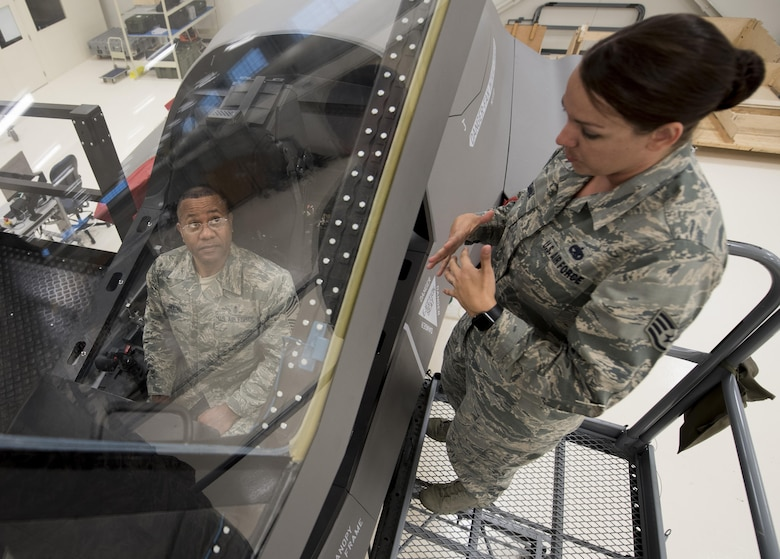 U.S. Air Force Staff Sgt. Amanda Dennis, F-35 Field Training Detachment egress instructor, explains an F-35 ejection seat maintenance trainer to Chief Master Sgt. David Brown, 19th AF command chief, Oct. 3, 2017, at Eglin Air Force Base, Fla. During Brown's visit at the 33rd Fighter Wing, Brown experienced the one-of-a-kind training facility where F-35 maintainers hone their craft by using state of the art equipment. (U.S. Air Force photo by Staff Sgt. Peter Thompson)