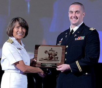 Vice Adm. Raquel Bono, Director, Defense Health Agency, presents Maj. (Dr.) Steven Schauer, of the U.S. Army Institute of Surgical Research at Joint Base San Antonio-Fort Sam Houston. with the 2017 Military Health System Research Symposium award for Outstanding Research Accomplishment (military/individual) Aug. 26.