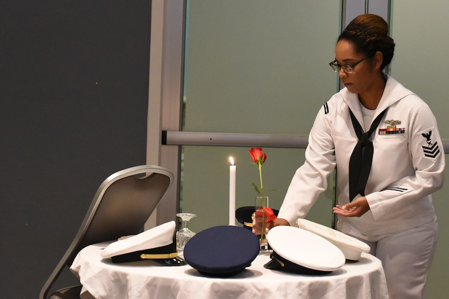 U.S. Navy Petty Officer 1st Class Diana Williams, Center for Information Warfare Training Detachment Goodfellow instructor, places a single rose on the POW/MIA table during the Navy Ball at the Event Center on Goodfellow Air Force Base, Texas Oct. 6, 2017. The POW/MIA table is set each ball in remembrance of those who are unable or longer able to join. (U.S. Air Force photo by Airman Zachary Chapman/Released)
