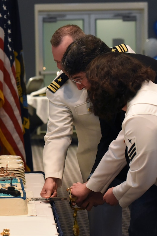 U.S. Navy Lt. Cmdr. Christopher Allen, Center for Information Warfare Training Detachment Goodfellow officer in charge, retired Master Chief Petty Officer Steven Chaney, and Cryptologic Technician Collection Seaman Madison Elliot, Center for Information Warfare Training Detachment Goodfellow trainee, cut the Navy birthday cake during the Navy Ball at the Event Center on Goodfellow Air Force Base, Texas Oct. 6, 2017. Tradition is to have the youngest and the oldest cut the cake, but in breaking tradition, Allen was allowed to join for his last Navy Ball at Goodfellow. (U.S. Air Force photo by Airman Zachary Chapman/Released)