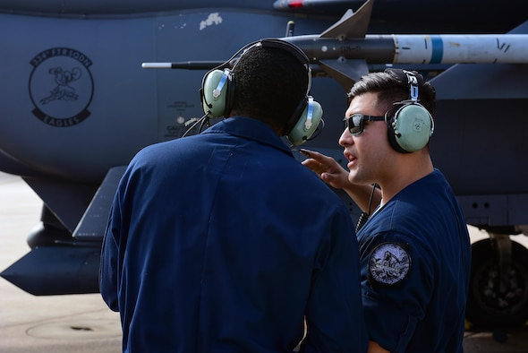 Staff Sgt. Daniel Solis-Reyes, 4th Aircraft Maintenance Squadron dedicated crew chief, right, instructs Airman 1st Class Germain Magloire, 4th AMXS crew chief, left, on how to launch an F-15E Strike Eagle, Oct. 4, 2017, at Seymour Johnson Air Force Base, North Carolina. Reyes was highlighted during Hispanic Heritage Month for being recognized as an outstanding leader and Airman by his coworkers and superiors. (U.S. Air Force photo by Airman 1st Class Kenneth Boyton)
