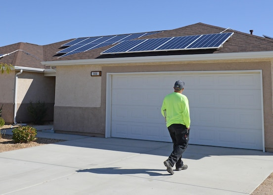 Contractors work to install solar panels on this house in the Tamarisk Plains neighborhood on Edwards Air Force Base. Workers will install solar panels on 368 homes on the base beginning with vacant homes first. (U.S. Air Force photo by Kenji Thuloweit)