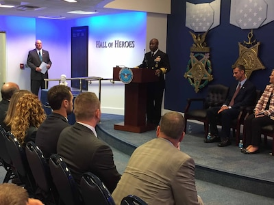 Navy Vice Adm. Kevin D. Scott, the Joint Staff's director of joint force development, congratulates the recipients chosen to share a $200,000 donation from the Newman's Own Foundation.
