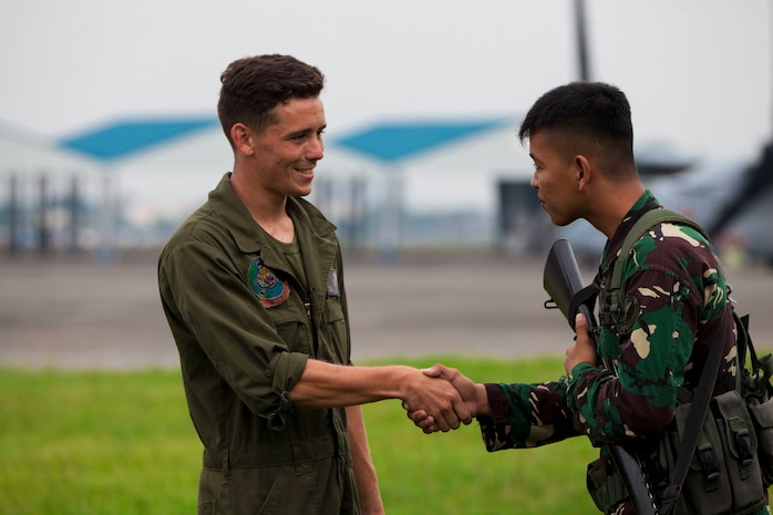 U.S. Marine Lance Cpl. Kleber Leaf, an airframes mechanic with Marine Medium Tiltrotor Squadron 262 (VMM-262), Marine Aircraft Group 36, 1st Marine Aircraft Wing, and Philippine Airman Second Class Arvin Neil D. Barmal, greet each other during an MV-22B Osprey tiltrotor aircraft maintenance repair on Clark Air Base during exercise KAMANDAG, Oct. 5, 2017. Bilateral exercises such as KAMANDAG increase the ability of the United States and the Philippines to rapidly respond and work together during real world terrorist or humanitarian crises, in order to accomplish the mission, support the local population and help mitigate human suffering. (U.S. Marine Corps Photo by Corporal Marimar M. Morales)