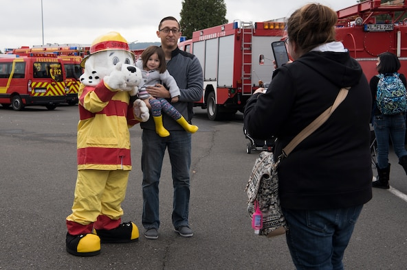 "Members of the Kaiserslautern Military Community take a photo with Sparky the fire dog during the Fire Prevention Week open house on Ramstein Air Base, Germany, Oct. 7, 2017. Fire Departments from Ramstein Village, Landstuhl, Carlsberg, and Technical Relief Foundation (THW) Kaiserslautern, participated in the parade and open house. This year's theme, ""Every second counts, plan two ways out!"" encourages families to have more than one exit plan in case of an emergency. (U.S. Air Force photo by Airman 1st Class Devin M. Rumbaugh)"