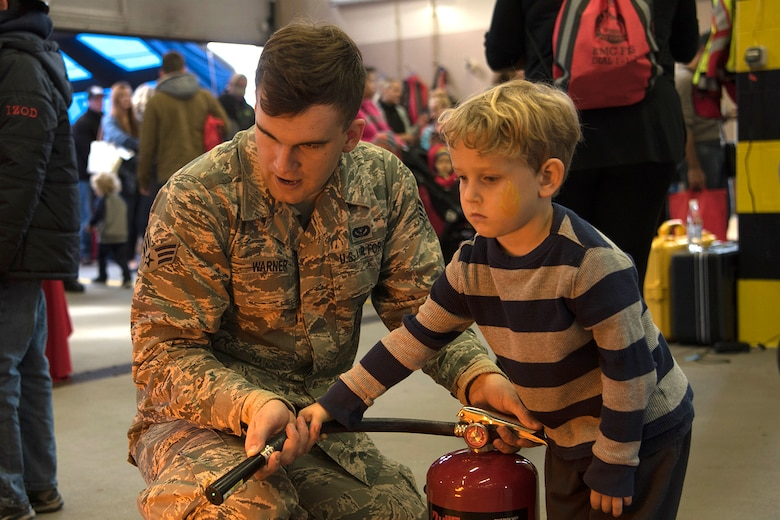 "U.S. Air Force Senior Airman Seth Warner, 86th Civil Engineer Squadron driver operator, helps a child from the Kaiserslautern Military Community put out a simulated fire during the Fire Prevention Week open house on Ramstein Air Base, Germany, Oct. 7, 2017. Fire Departments from Ramstein Village, Landstuhl, Carlsberg, and Technical Relief Foundation (THW) Kaiserslautern, participated in the parade and open house. This year's theme, ""Every second counts, plan two ways out!"" encourages families to have more than one exit plan in case of an emergency. (U.S. Air Force photo by Airman 1st Class Devin M. Rumbaugh)"