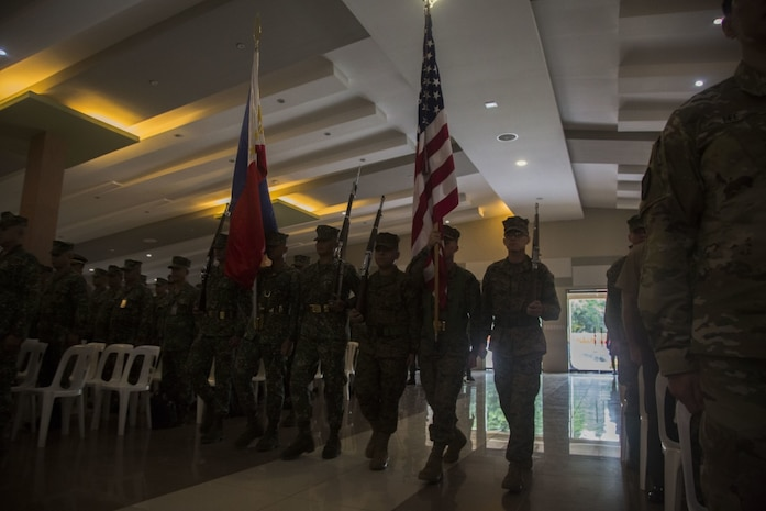 """A color guard comprised of U.S. and Philippine Marines present their national colors at Marine Barracks Rudiardo Brown, Taguig, Philippines, Oct. 2, to celebrate the beginning of KAMANDAG. KAMANDAG is an acronym for the Filipino phrase """"Kaagapay Ng Maddirigma Ng Dagat,"""" which translates to """"Cooperation of Warriors of the Sea."""" This bilateral exercise increases the ability of the U.S. and the Philippines to rapidly respond to terrorist threats or humanitarian crises. (U.S. Marine Corps Photo by Lance Cpl. Nathan Maysonet)"""