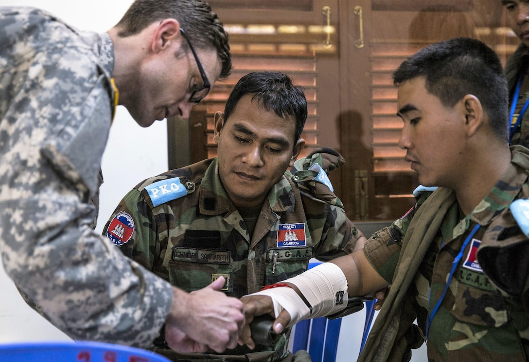 Army Capt. Derek Derkacs explains to members of the Royal Cambodian Armed Forces how to splint a fracture.