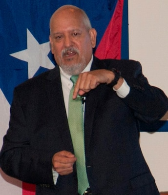 IMAGE: DAHLGREN, Va. (Sept. 28, 2017) - Hispanic Heritage Observance keynote speaker Lance Carrington encourages his audience to pray for the residents of Puerto Rico after Hurricane Maria devastated the island, and to pray for those living in Texas, the Gulf Coast, and Florida who are recovering from Hurricanes Harvey and Irma. Carrington – retired from the Senior Executive Service (SES) as a special agent for NASA and the U.S. Postal Service – recounted his life and career which included service in the Army as a reserve chief warrant officer. He retired from the Army reserves on Oct. 1, 2017 after more than 35 years of active duty, National Guard, and reserve service. He is currently executive director of the Catholic Diocese of Arlington's Guadalupe Free Clinic in Colonial Beach, Va. The clinic serves the indigent and medically-uninsured population in Westmoreland County and Colonial Beach, on the Northern Neck of Virginia.
