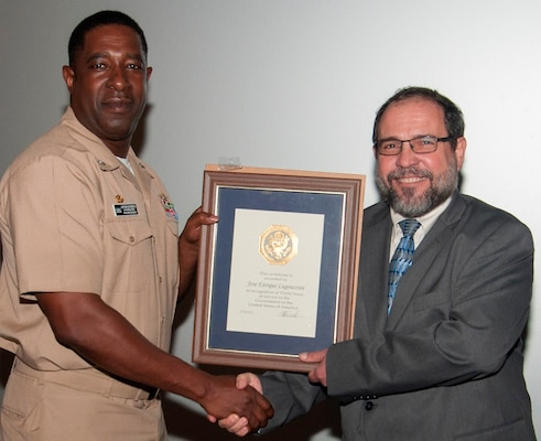 "IMAGE: DAHLGREN, Va. (Sept. 28, 2017) - Naval Surface Warfare Center Dahlgren Division (NSWCDD) Commanding Officer Capt. Godfrey 'Gus' Weekes presents NSWCDD senior engineer Jose Lugo with a certificate recognizing Lugo's 30 years of government service before military, government civilians, and defense contractors celebrating Hispanic Heritage Month at the Naval Support Facility Dahlgren theater. ""As we celebrate this Heritage Month, I want you all to remember that in order to shape the bright future of America, each one of us has to be a point of light,"" Lugo told the audience after receiving his certificate. ""We have to brighten the day of everybody around us and we have to inspire those who follow us, and in doing so we will improve our future.""  At this year's event, personnel from NSF Dahlgren and tenant commands gathered at the base theater to join the Navy and nation while celebrating and reflecting on the theme ""Shaping the Bright Future of America."""
