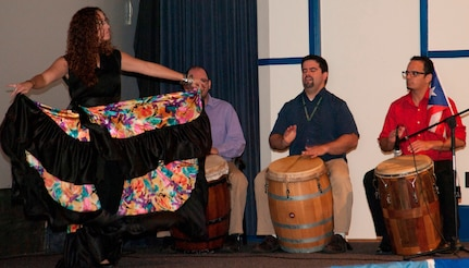 IMAGE: DAHLGREN, Va. (Sept. 28, 2017) - Isha Renta, a National Oceanic and Atmospheric Administration meteorologist, dances to Bomba music played by Semilla Cultural (Cultural Seed) volunteers at the Naval Surface Warfare Center Dahlgren Division (NSWCDD) sponsored Hispanic Heritage Observance. The performers on stage are NSWCDD scientists and engineers. Renta founded the Semilla Cultural nonprofit organization to cultivate a community that embraces diversity by educating, promoting and disseminating Puerto Rican culture and traditions. The Bomba is a dialogue between the primo drummer and the dancer where the dancer dictates the rhythm of the percussion and the drummer follows the dancer's body and skirt movements. The primo drummer improvises as the dancer challenges the drummer to follow the dancer's improvised movements, called piquetes. Bomba singing is based on a call-response structure in which the lead singer begins the song and is answered by a melody sung by the chorus.