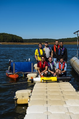 Engineers from Naval Surface Warfare Center, Carderock Division launch an unmanned surface vehicle in Triadelphia Reservoir near Brighton Dam in Brookville, Md., that will function as a relay for an unmanned underwater vehicle conducting bathymetry in the reservoir Sept. 28, 2017. Staff from the Naval Meteorological and Oceanography Command controlled the collaborative autonomous demonstration via satellite connection from their headquarters at John C. Stennis Space Center in Mississippi with assistance from the Autonomous Vehicle and Instrumentation Group and other Carderock personnel. Rear row, left to right: electrical engineer Woody Pfitsch (Code 863), program officer Judah Milgram (Code 882), hardware engineer Alex Punzi (Code 863), group leader Jim Rice (Code 8633); front row, left to right: electrical engineer Ben Gordon (Code 8633), control systems engineer Matt Greytak (Code 861) and mechanical engineer Kyle Corfman (Code 863). (U.S. Navy photo by Ryan Hanyok/Released)