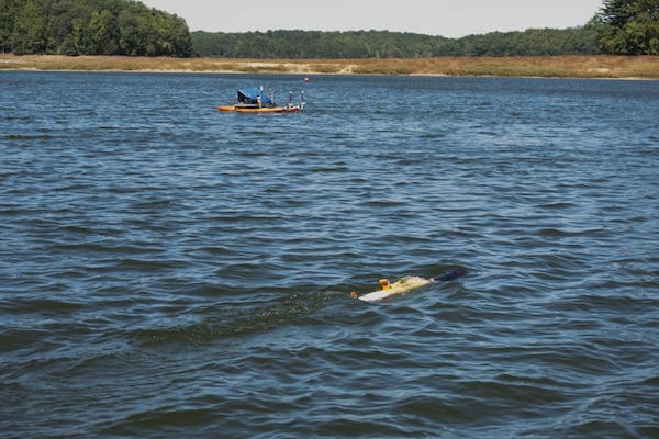 A kayak catamaran unmanned surface vehicle follows an unmanned underwater vehicle in Triadelphia Reservoir in Brookeville, Md., Sept. 28, 2017, during a joint integrated autonomous demonstration with engineers from the Naval Oceanographic Office at the John C. Stennis Space Center in Mississippi controlling the test with supervision and assistance from colleagues on station from Naval Surface Warfare Center, Carderock Division™s Autonomous Vehicle and Instrumentation Group. (U.S. Navy photo by Ryan Hanyok/Released)