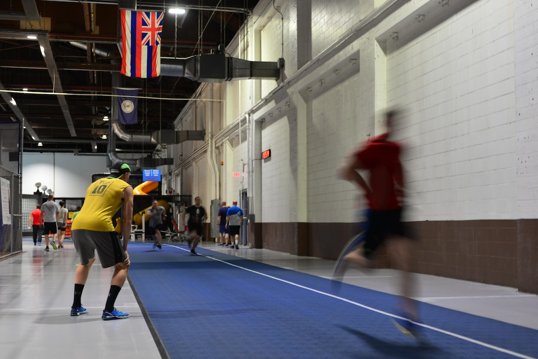 Airman 1st Class Crayton Noe, founder and lead instructor of the Offutt Run Clinic, watches clinic attendees sprint down the track at the Offutt Field House at Offutt Air Force Base, Nebraska, Sept. 29, 2017.