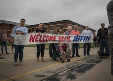 Family of Virginia Air National Guard Staff Sgt. Jeff Greenquist, holds a welcome home sign, celebrating his return from the Middle East at Joint Base Langley- Eustis, Va., Oct. 12, 2017. Greenquist is a low observable technician from the 192nd Maintenance Squadron and was deployed with the 1st Fighter Wing for six months. The deployment consisted of F-22 Raptors and Airmen representing the 1st FW in Operation Inherent Resolve against ISIS. (U.S. Air Force photo by Staff Sgt. Carlin Leslie)