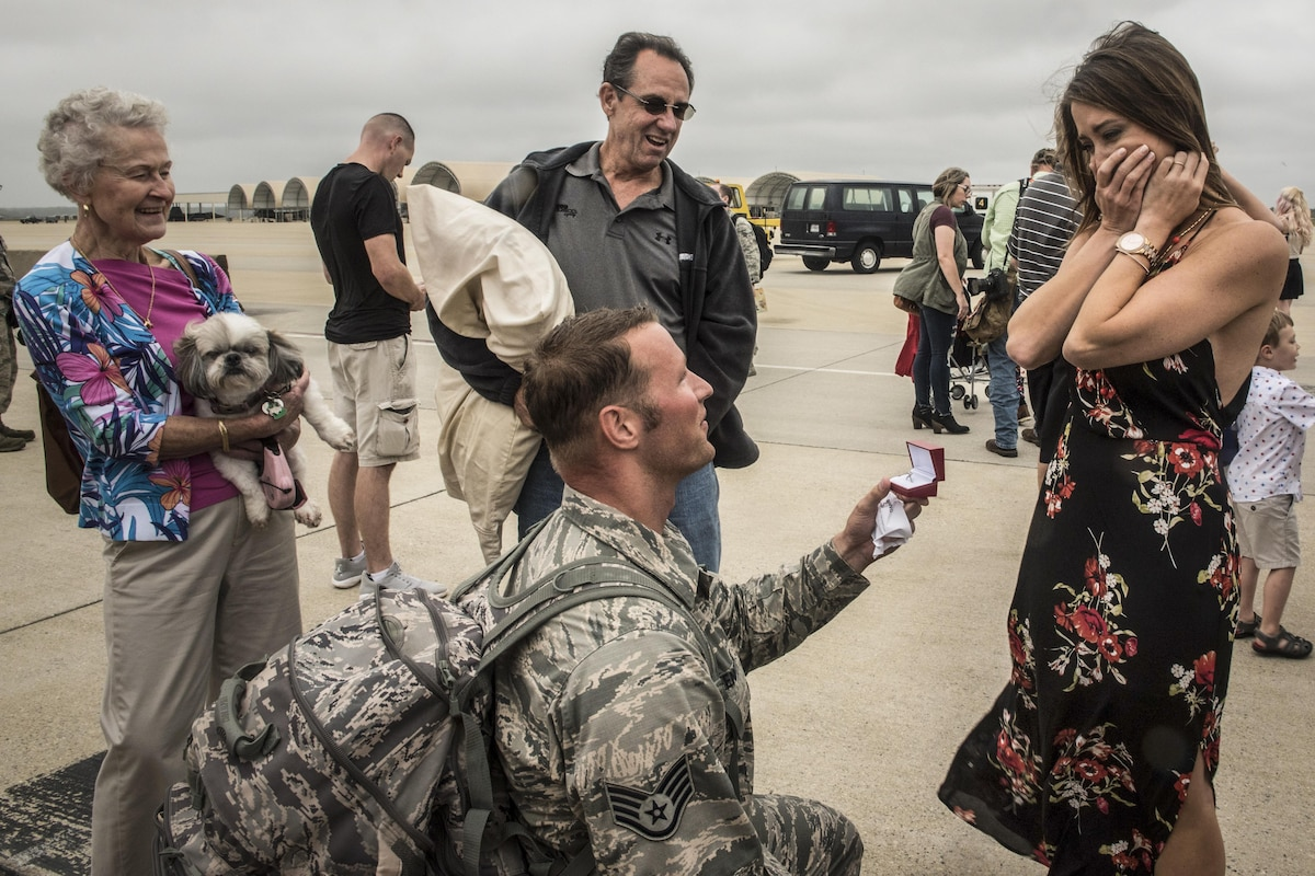 An airman kneels to proposed to his girlfriend at a base.