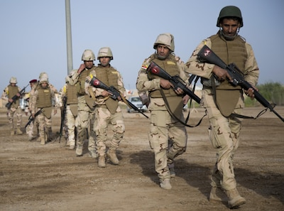 Iraqi security forces walk to a checkpoint training area at Camp Taji, Iraq.
